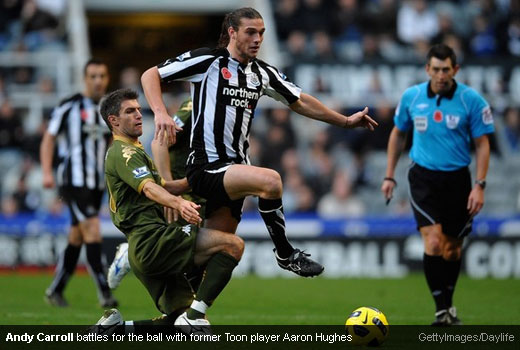 Andy Carroll battles for the ball with former Toon player Aaron Hughes