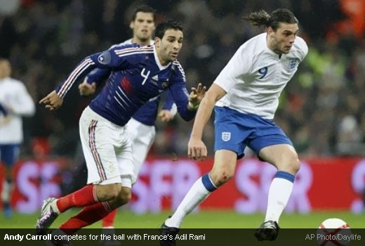 Andy Carroll competes for the ball with France's Adil Rami