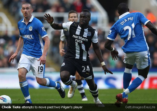 Cheik Tiote attempts to move past two Wigan's player [MagpiesZone/GettyImages/DayLife]