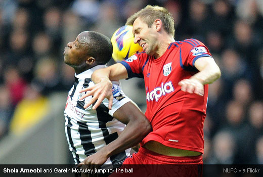 Shola Ameobi and Gareth McAuley jump for the ball